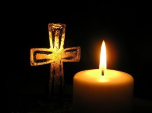 golden-cross-and-candle-in-dark-surroundings